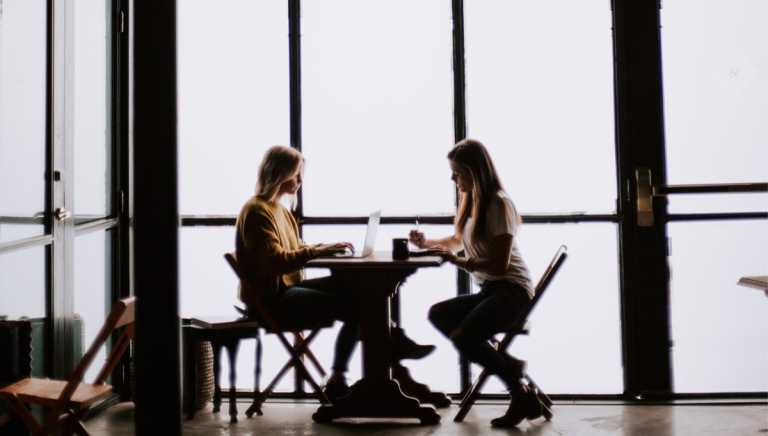 two women talking around a table